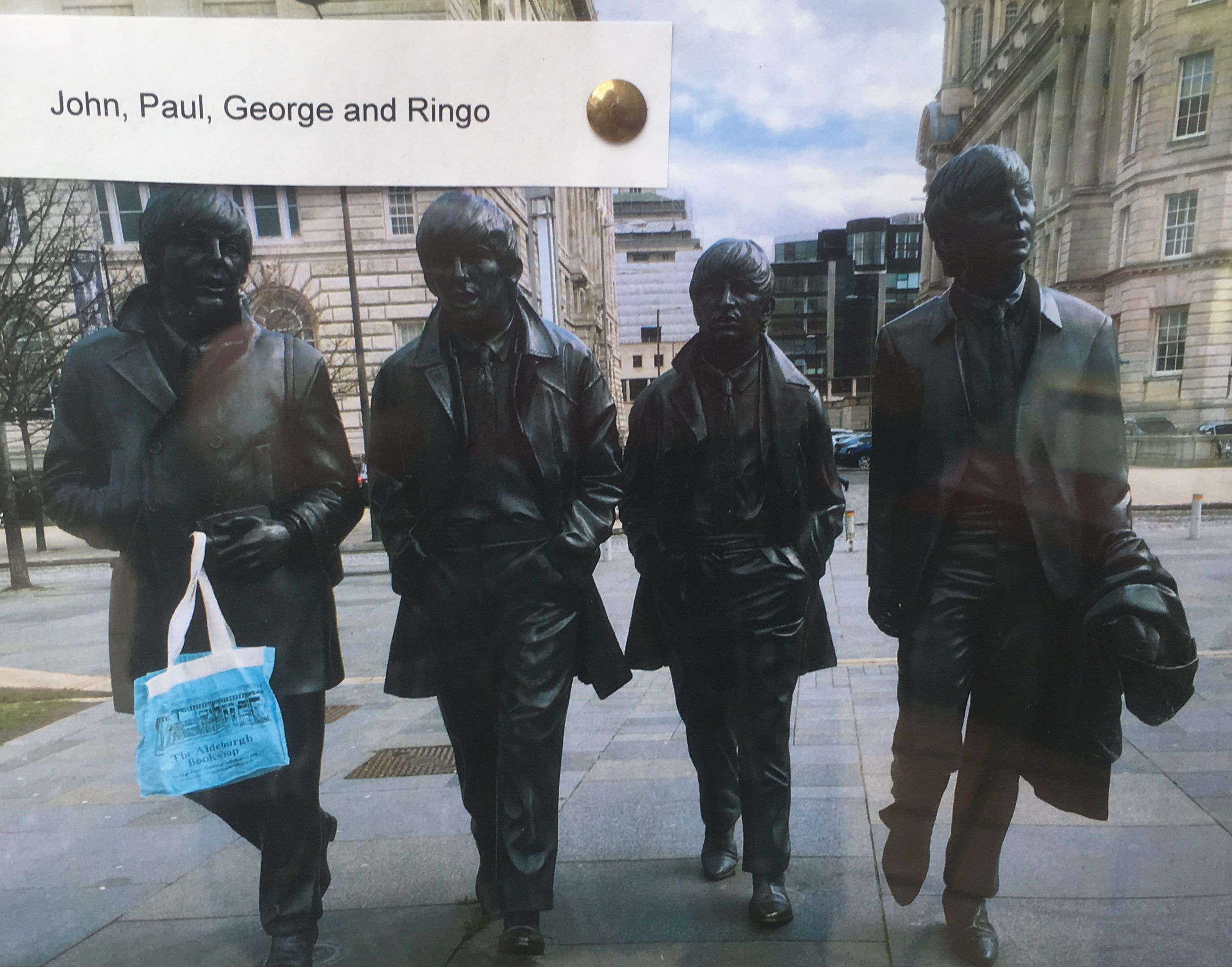 The Beatles statue in Liverpool, with Paul holding an Aldeburgh Bookshop tote bag